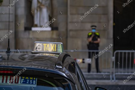 The TAXI light indicator on the roof of a vehicle is seen in front of the entrance of the Barcelona City Council, guarded by an agent of the Barcelona Urban Guard. Fourth day of protest of the Taxi sector in Barcelona today  in front of the City Council to request public financial aid against Covid19 and new anti-intrusion regulations.