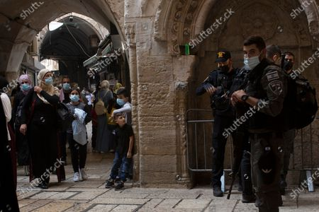 Child looks towards Israeli police standing guard as Palestinians head to the Al-Aqsa Mosque for prayers marking Moulid al-Nabi, the Prophet Muhammad's birthday, in the Old City of Jerusalem