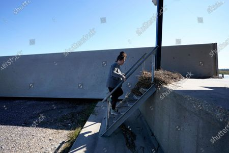 Stock Picture of An employee of Bayou Caddy Fisheries walks up stairs where marsh grass remains from a storm surge, next to an overturned tractor trailer, in the Aftermath of Hurricane Zeta in Lakeshore, Miss