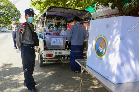 Policemen wearing face masks stand on guard beside the mobile advance voting car. Union Election commission makes the advance voting for the elderly persons who are over (60) years old. Voters over the age of (60) in Mandalay's Aung Myay Thar Zan Township will be able to cast their ballots in advance on the morning of October 29. Myanmar's general election will be held on November 8.