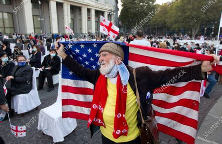 Supporters of the United National Movement party holds an American national flag as he attends a parliamentary election campaign rally in Tbilisi, Georgia, . The parliamentary elections will take place in Georgia on Saturday, Oct. 31, 2020