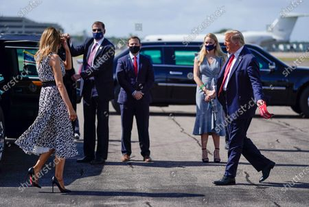 President Donald Trump gestures to first lady Melania Trump as he arrives at Tampa International Airport, in Tampa