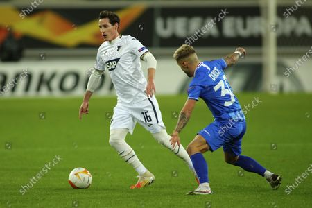 Hoffenheim's Sebastian Rudy, left, vies for the ball with Gent's Niklas Dorsch during the Europa League Group L soccer match between Gent and Hoffenheim at the KAA Gent stadium in Gent, Belgium