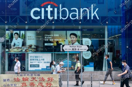 Pedestrians wearing masks walk past the American multinational investment bank and financial services corporation Citibank or Citi branch in Hong Kong.