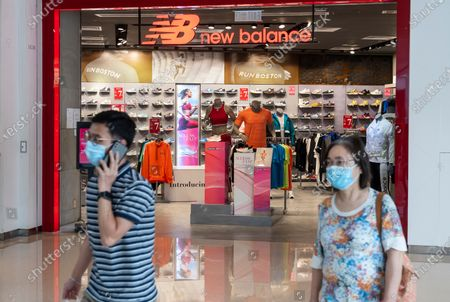 People wearing face masks walk past an American footwear brand New Balance store and logo seen in Hong Kong.