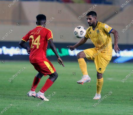 Al-Qadisiyah's player Hassan Abu Sharara (L) in action against Al-Taawoun's Fahad Ayed Al-Rashidi (R) during the Saudi Professional League soccer match between Al-Qadisiyah and Al-Taawoun at Prince Saud Bin Jalawy Stadium, in Dammam, Saudi Arabia, 29 October 2020.