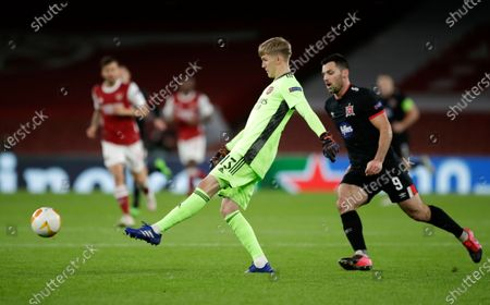 Arsenal's goalkeeper Runar Alex Runarsson kicks the ball clear of Dundalk's Patrick Hoban during the Europa League Group B soccer match between Arsenal and Dundalk at the Emirates Stadium in London, Thursday, Oct. 29. 2020