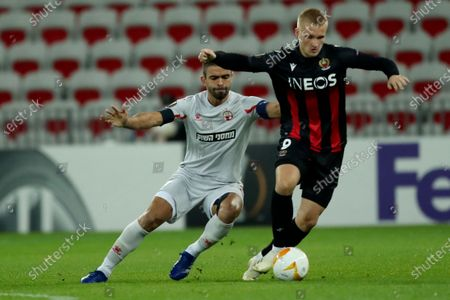 Stock Photo of Nice's Kasper Dolberg, right, vies for the ball with Hapoel Beer-Sheva's Miguel Vitor during the Europa League Group C soccer match between OGC Nice and Hapoel Beer-Sheva at the Allianz Riviera stadium in Nice, France