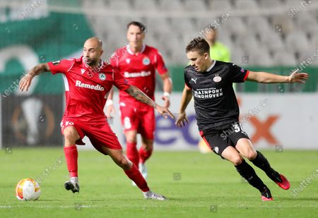 Fotios Papoulis (L) of Omonia in action against Ryan Thomas (R) of PSV during the UEFA Europa League group E soccer match between Omonia Nicosia and PSV Eindhoven in Nicosia, Cyprus, 29 October 2020.