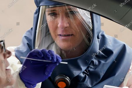 Salt Lake County Health Department public health nurse Lee Cherie Booth performs a coronavirus test outside the Salt Lake County Health Department in Salt Lake City. Utah Gov. Gary Herbert and health officials issued repeated pleas for social distancing and mask usage on Thursday, Oct. 29, 2020, as hospitals grow closer to implementing crisis care protocols amid a record-breaking coronavirus surge