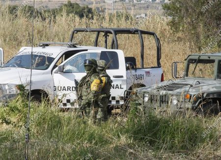 Soldiers stand guard near the site where a mass graves were found in Salvatierra, Guanajuato state, Mexico, . A Mexican search group said Wednesday it has found 59 bodies in a series of clandestine burial pits in the north-central state of Guanajuato, and that more could still be excavated