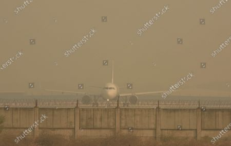 A passenger aircraft parked on a taxiway amid heavy haze in the morning at Indira Gandhi International (IGI) Airport, on October 29, 2020 in New Delhi, India.