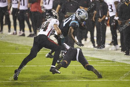 Carolina Panthers wide receiver Robby Anderson (11) is upended by Atlanta Falcons cornerback Isaiah Oliver (26) during an NFL football game, in Charlotte, N.C