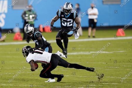 Carolina Panthers defensive end Brian Burns jumps over Atlanta Falcons wide receiver Julio Jones during the first half of an NFL football game, in Charlotte, N.C