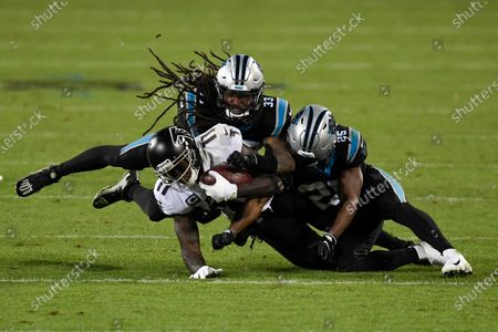 Atlanta Falcons wide receiver Julio Jones I is tackled by Carolina Panthers free safety Tre Boston and cornerback Troy Pride during the second half of an NFL football game, in Charlotte, N.C