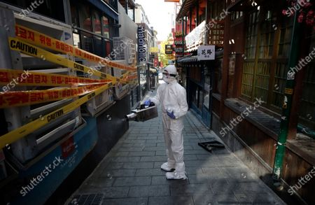 Health official from the district office wearing a protective gear disinfects as a precaution against the coronavirus in Seoul, South Korea