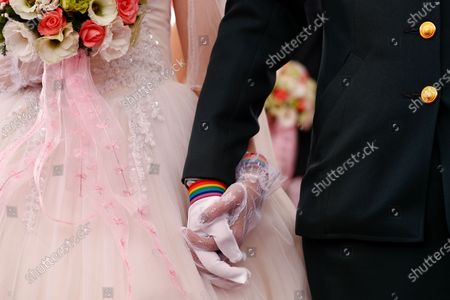 Couple Ying-Hsuan Chen (R) and Li-Chen Li(L) hold hands while wearing rainbow wrist bands during a military mass wedding in Taoyuan, Taiwan, 30 October 2020. Two same sex couples tied the knot as part of a mass wedding held by the Taiwan military. According to news reports, it is the first time that same sex couples got married as part of a mass wedding held by the military since Taiwan became the first country in Asia to legalize same-sex marriage in May 2019.