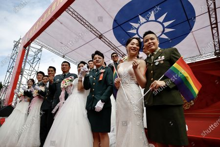 (R to L) Couples Yi Wang and Yumi Meng, Ying-Hsuan Chen and Li-Chen Li pose for a photograph next to other military couples during a military mass wedding in Taoyuan, Taiwan, 30 October 2020. Two same sex couples tied the knot as part of a mass wedding held by the Taiwan military. According to news reports, it is the first time that same sex couples got married as part of a mass wedding held by the military since Taiwan became the first country in Asia to legalize same-sex marriage in May 2019.