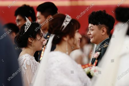 Stock Photo of Couple Ying-Hsuan Chen (R) and Li-Chen Li(L) react during a military mass wedding in Taoyuan, Taiwan, 30 October 2020. Two same sex couples tied the knot as part of a mass wedding held by the Taiwan military. According to news reports, it is the first time that same sex couples got married as part of a mass wedding held by the military since Taiwan became the first country in Asia to legalize same-sex marriage in May 2019.