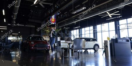 Hold For Biz-New Car Sales-A shopper checks her mobile device amid 2020 Clubman models on the showroom floor at a Mini dealership, in Highlands Ranch, Colo