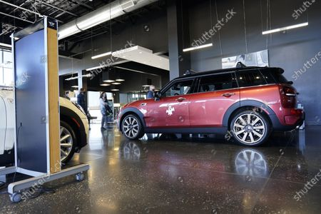 Hold For Biz-New Car Sales-A sales associate works with a pair of shoppers amid a sea of 2020 Clubman models on display at a Mini dealership, in Highlands Ranch, Colo
