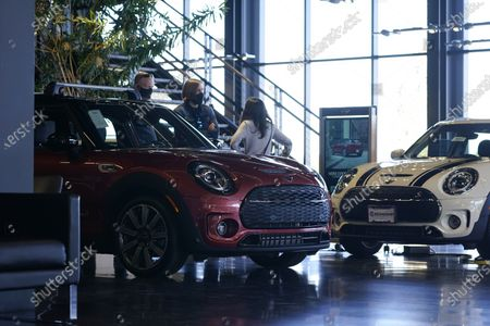 Hold For Biz-New Car Sales-A sales associate works with a pair of shoppers considering 2020 Clubman models on display at a Mini dealership, in Highlands Ranch, Colo