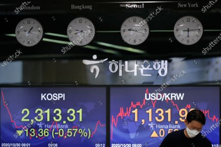 Currency trader walks by screens showing the Korea Composite Stock Price Index (KOSPI), left, and the foreign exchange rate between U.S. dollar and South Korean won at the foreign exchange dealing room in Seoul, South Korea, . Asian stocks sank Friday as investors looked ahead to next week's U.S. presidential election and weighed the chances of economic stimulus from Washington and Europe