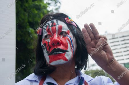 """A protester with a face painting makes the three-finger salute during the demonstration. . Thousands of pro-democracy protesters took the streets at Silom demanding the resignation of Thailand Prime Minister and the reform of the monarchy. The protest was organised by the free youth Group in the theme """"People's Runway"""" with a mock fashion """"red carpet"""", dancing, performing, show and music."""