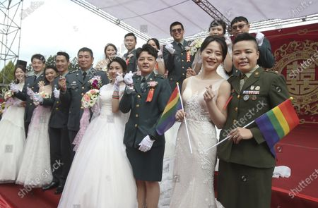 Two lesbian couples, from right to left, Yi Wang and Yumi Meng, Chen Ying-hsuan and Li Li-chen pose for a photo during a military mass weddings ceremony in Taoyuan city, northern Taiwan, . The two lesbian couples tied the knot in a mass ceremony held by Taiwan's military on Friday in a historic step for the island. Taiwan is the only place in Asia to have legalized gay marriage, passing legislation in this regard in May 2019
