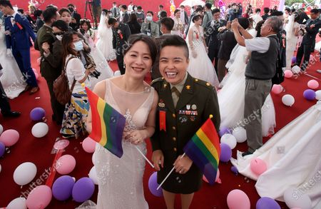 Lesbian couple Yi Wang, right, and Yumi Meng pose during a military mass weddings ceremony in Taoyuan city, northern Taiwan, . Two lesbian couples tied the knot in a mass ceremony held by Taiwan's military on Friday in a historic step for the island. Taiwan is the only place in Asia to have legalized gay marriage, passing legislation in this regard in May 2019