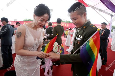 Lesbian couple Yumi Meng, left, puts a ring on Yi Wang' s finger during a military mass weddings ceremony in Taoyuan city, northern Taiwan, . Two lesbian couples tied the knot in a mass ceremony held by Taiwan's military on Friday in a historic step for the island. Taiwan is the only place in Asia to have legalized gay marriage, passing legislation in this regard in May 2019