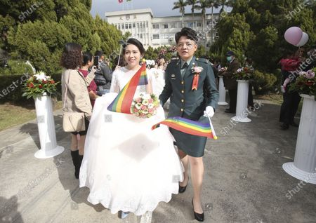 Illustration libre de droits de Lesbian couple Chen Ying-hsuan, right, and Li Li-chen attend a military mass weddings ceremony in Taoyuan city, northern Taiwan, . Two lesbian couples tied the knot in a mass ceremony held by Taiwan's military on Friday in a historic step for the island. Taiwan is the only place in Asia to have legalized gay marriage, passing legislation in this regard in May 2019