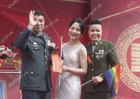 Lesbian couple Yi Wang, right, Yumi Meng and General Chen Pao-Yu pose for a photo during a military mass weddings ceremony in Taoyuan city, northern Taiwan, . Two lesbian couples tied the knot in a mass ceremony held by Taiwan's military on Friday in a historic step for the island. Taiwan is the only place in Asia to have legalized gay marriage, passing legislation in this regard in May 2019