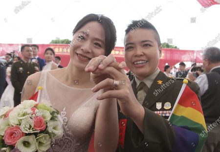 Lesbian couple Yi Wang, right, and Yumi Meng show their wedding rings during a military mass weddings ceremony in Taoyuan city, northern Taiwan, . Two lesbian couples tied the knot in a mass ceremony held by Taiwan's military on Friday in a historic step for the island. Taiwan is the only place in Asia to have legalized gay marriage, passing legislation in this regard in May 2019