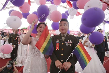 Lesbian couple Yi Wang, right, and Yumi Meng cheer during a military mass weddings ceremony in Taoyuan city, northern Taiwan, . Two lesbian couples tied the knot in a mass ceremony held by Taiwan's military on Friday in a historic step for the island