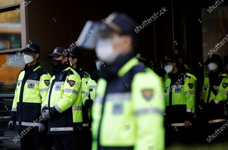South Korean police officers wearing face masks as a precaution against the coronavirus, stand guard in Seoul, South Korea