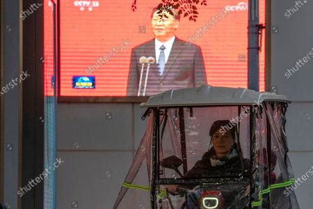 "Woman in a covered tricycle rides past a screen showing Chinese President Xi Jinping in Beijing on . China will promote ""technological self-reliance"" under the ruling Communist Party's latest five-year plan but will open further to trade, officials said Friday"
