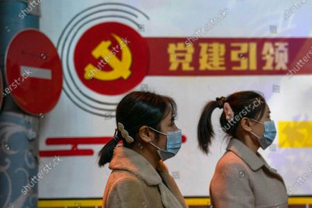 "Residents wearing masks pass by the Communist party logo and the slogan ""Party building leadership"" in Beijing on . China will promote ""technological self-reliance"" under the ruling Communist Party's latest five-year plan but will open further to trade, officials said Friday"