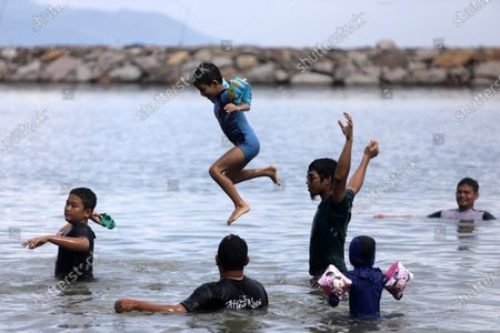 Children swim amid the COVID-19 pandemic at Ule Lhuee beach, Aceh, Indonesia, 30 October 2020. Tourism is the sector that has suffered the most losses due to travel restrictions by all countries globally due to the coronavirus pandemic. Indonesia has lost around IDR 85 trillion (5.87 US billion) in tourism revenue so far this year.