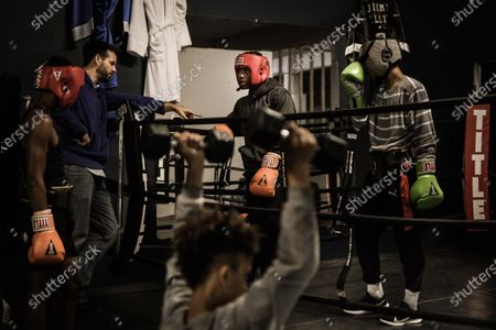 Young boxers Demontaze 'Juicy' Duncan (2-R), Troy (L) and Nassel (R) listen to their coach Nicholas Bareis (2-L) during a training session at the Champ Camp boxing gym, in Louisville, USA, 26 October 2020 (issued 30 October 2020). For young Louisville boxing 'champion' Demontaze 'Juicy' Duncan in politics as in boxing there is also a winner and a loser and, therefore, he's in 'combat' against US President Donald J. Trump. Because of Muhammad Ali, Louisville, in the state of Kentucky, is a city marked by boxing especially among the most disadvantaged populations in the west and south, along the Ohio River.