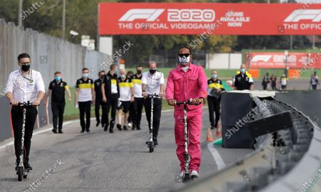 Mercedes driver Lewis Hamilton of Britain, center, wears a protective face mask as he rides an electric scooter during track inspection ahead of Sunday's Emilia Romagna Formula One Grand Prix, at the Dino and Enzo Ferrari racetrack, in Imola, Italy