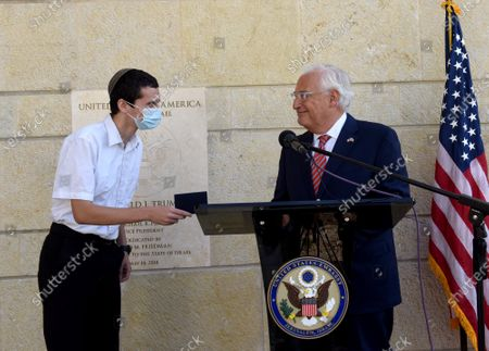 Stockfoto van United Sates Ambassador to Israel David Friedman (R) presents Menachem Zivotosky (L) his passport during an event at the US Embassy in Jerusalem, Israel, October 30, 2020.  US citizens born in Jerusalem can now list Israel as their birthplace in American passports after of President Donald Trump listed Jerusalem as the capitol of Israel moved the USA embassy there.
