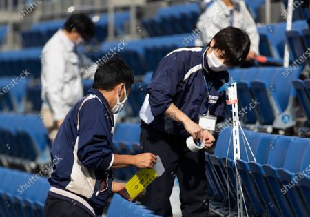 Stadium crew members install a device to detect carbon dioxide in the seats of a baseball stadium, home for the Yokohama DeNA BayStars, in Yokohama, south of Tokyo on . The device was introduced during a media tour before a Japanese professional baseball league game between the Hanshin Tigers and the DeNA BayStars on Friday