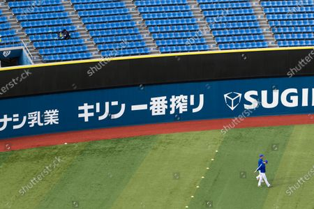 Stadium crew member, upper left, installs a device to detect carbon dioxide in the seats of a baseball stadium, home for the Yokohama DeNA BayStars, in Yokohama, south of Tokyo on . The device was introduced during a media tour before a Japanese professional baseball league game between the Hanshin Tigers and the DeNA BayStars on Friday