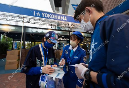 Fan tries to show a mobile phone app called Cocoa created by the Japanese health ministry to help curb the coronavirus as she enters a baseball stadium before a Japanese professional baseball league game in Yokohama, south of Tokyo on