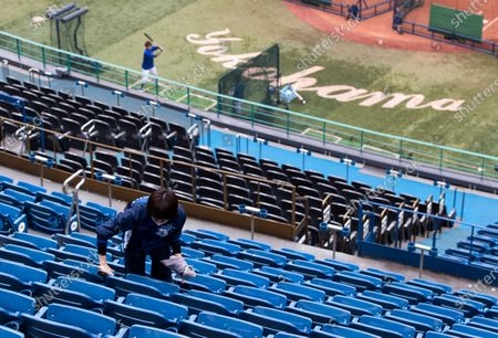 Nao Moteki, a part-time stadium crew member, wipes seats of a baseball stadium, home for the Yokohama DeNA BayStars, seen during a media tour in Yokohama, south of Tokyo on . The tour was held to introduce device installed at the stadium to record behaviors of baseball audience members during a game for coronavirus control