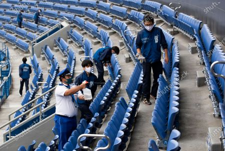 Stadium crew members clean seats of a baseball stadium, home for the Yokohama DeNA BayStars, seen during a media tour in Yokohama, south of Tokyo on . The tour was held to introduce device installed at the stadium to record behaviors of baseball audience members during a game for coronavirus control