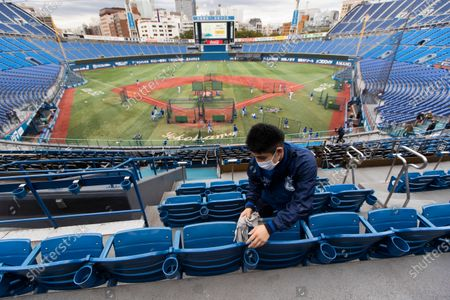 Atsuhiro Tanabe, a part-time stadium crew member, wipes seats of a baseball stadium, home for the Yokohama DeNA BayStars, seen during a media tour in Yokohama, south of Tokyo on . The tour was held to introduce device installed at the stadium to record behaviors of baseball audience members during a game for coronavirus control