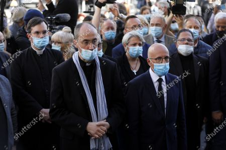 Father Franklin Parmentier (L) and member of the French Parliament Eric Ciotti (R) pay their respect to the victims of the knife attack at a makeshift memorial at the entrance of the Notre Dame Basilica church in Nice, France, 30 October 2020. Three people have died in a terror attack. The attack comes less than a month after the beheading of a French middle school teacher in Paris on 16 October.