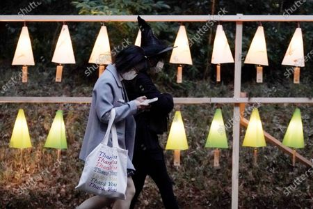 Visitors walk past lanterns and illuminated decoration being lit up to mark the 100th anniversary of the Meiji Jingu Shinto Shrine in Tokyo . Meiji Jingu, was built to pay tribute to the Emperor Meiji and Empress Shoken in 1920